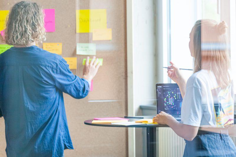 Designer ordnen Post-it-Ideen an einer Wand während eines Workshops.