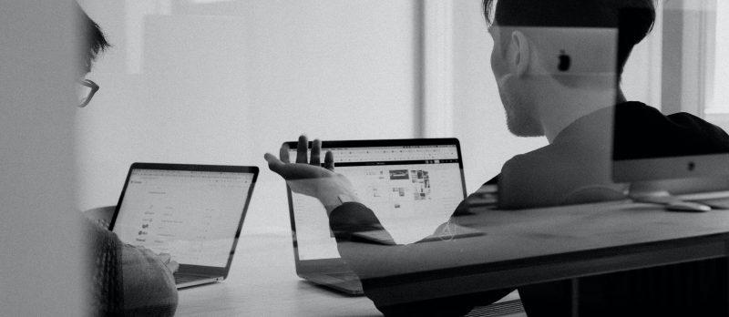 Designer arbeiten gemeinsam an Laptops.